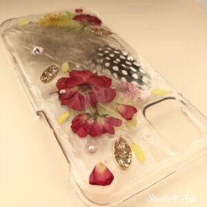 他店には無い「ふわふわの羽」を封じ込めたスマホケース!Studio*Askオリジナル商品です。紅いミニバラとレースフラワーが羽に花を添えています。